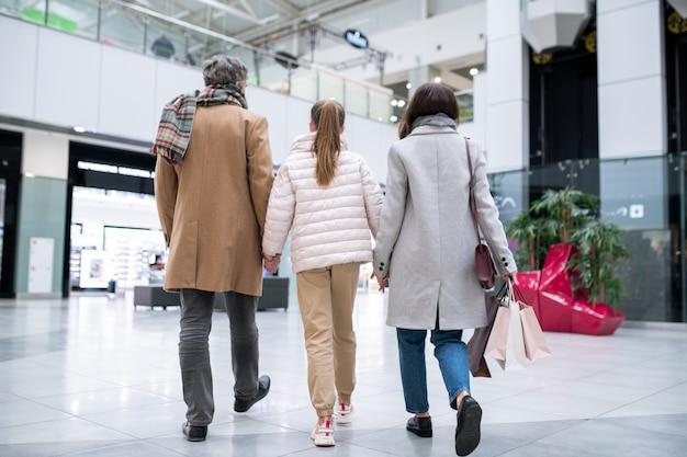 Vista traseira de um casal e sua filha em roupas casuais descendo o centro comercial contemporâneo após as compras