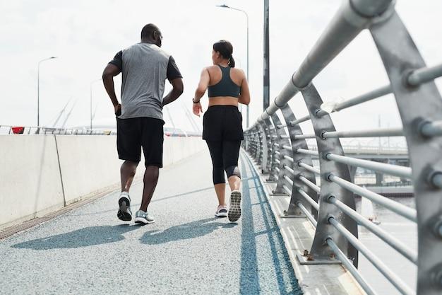 Vista traseira de um casal esportivo em roupas esportivas correndo juntos ao longo da ponte pela manhã