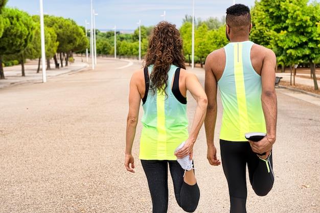 Vista traseira de um casal fazendo exercícios de alongamento nas pernas