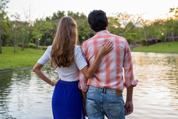 Vista traseira de um casal multiétnico em pé e se divertindo