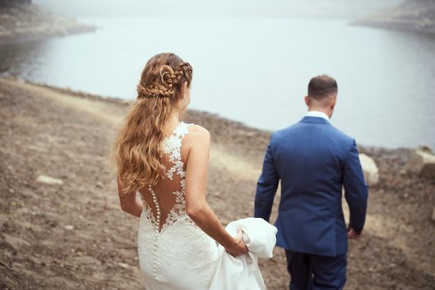 Vista traseira de um casal recém-casado caminhando em direção ao lago em um dia de nevoeiro