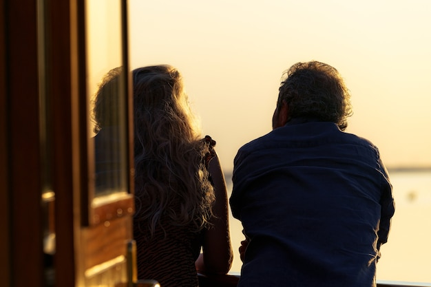Vista traseira de um casal romântico olhando para o convés de um barco durante o pôr do sol