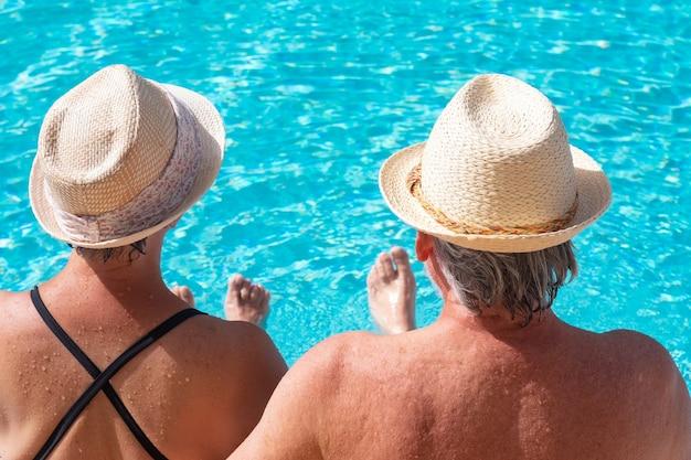 Vista traseira de um casal sênior caucasiano sentado à beira da piscina com os pés na água