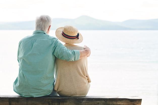 Vista traseira de um casal sênior sereno em trajes casuais, olhando para o lago enquanto relaxa à beira-mar em um dia de verão