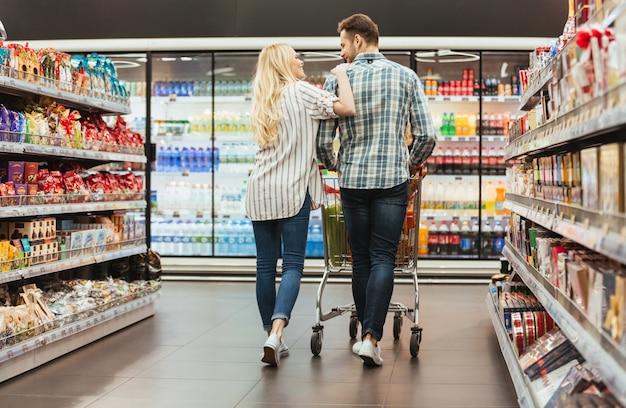 Vista traseira de um casal sorridente andando com um carrinho