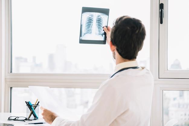 Vista traseira, de, um, doutor masculino, examinando, radiografia tórax