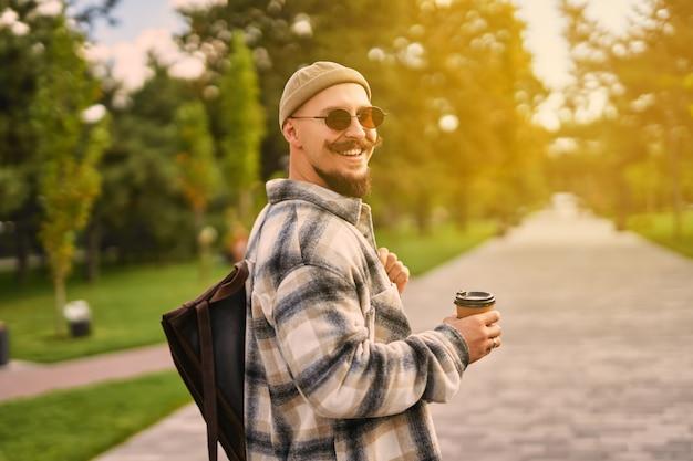 Vista traseira de um estudante barbudo hippie feliz bebe café enquanto caminha no dia de descanso do parque urbano da cidade