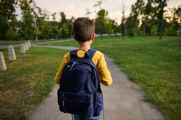 Vista traseira de um estudante com mochila na mochila, caminhando no caminho em um parque público, indo para casa depois da escola