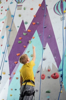 Vista traseira de um estudante em roupas esportivas apontando para cima em frente a um equipamento de escalada com cordas e pequenas pedras