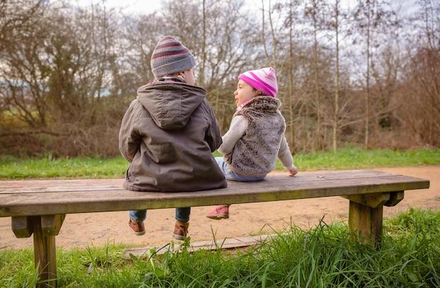 Vista traseira de um feliz menino e uma menina conversando e brincando, sentados em um banco de madeira no parque