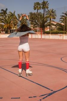 Vista traseira, de, um, femininas, patinador, esticar, dela, mãos, ficar, ligado, a, corte