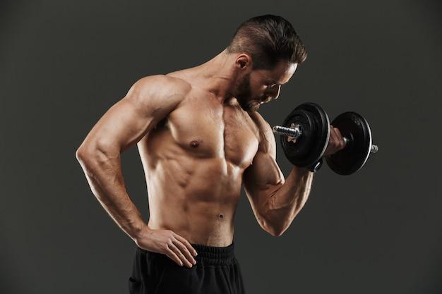 Vista traseira de um fisiculturista muscular levantando halteres pesados
