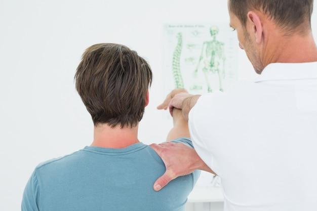 Vista traseira, de, um, fisioterapeuta, esticar, um, homens, braço
