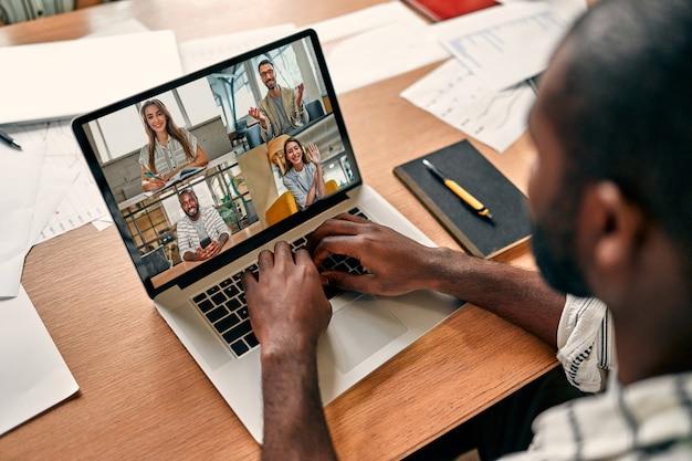 Vista traseira de um funcionário afro-americano com videochamada com colegas em briefing on-line, trabalhador do sexo masculino fazendo conferência de webcam em grupo com colegas em um laptop moderno em casa