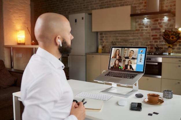 Vista traseira de um funcionário do sexo masculino que está trabalhando remotamente em uma videoconferência de negócios em um laptop em casa.
