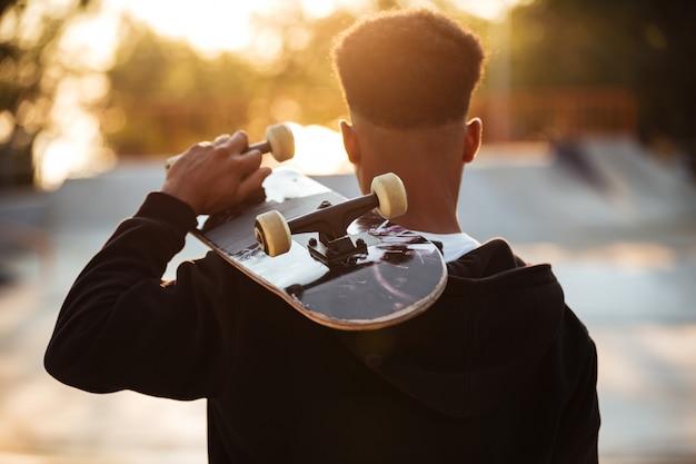 Vista traseira de um garoto adolescente masculino segurando o skate