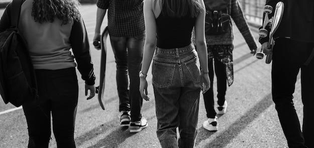 Vista traseira de um grupo de amigos de escola caminhando ao ar livre.