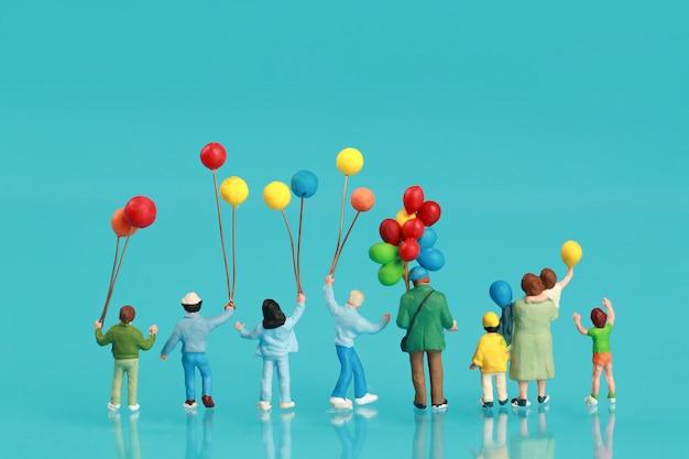 Vista traseira de um grupo de família feliz está se divertindo e segurando balão