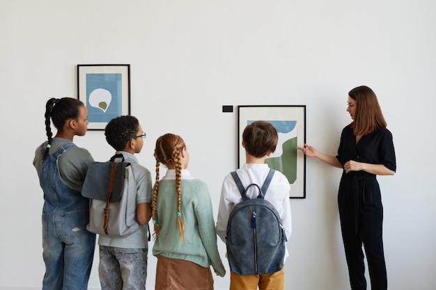 Vista traseira de um grupo diversificado de crianças ouvindo uma guia turística feminina enquanto visitava a galeria de arte moderna, copie o espaço