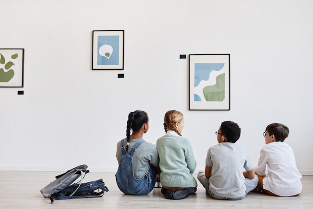 Vista traseira de um grupo diversificado de crianças sentadas no chão na galeria de arte moderna discutindo pinturas, copie o espaço