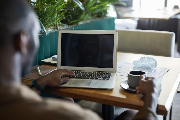 Vista traseira de um homem afro-americano moderno, trabalhando com um laptop em branco, enquanto está sentado à mesa no interior do café verde amigável, copie o espaço