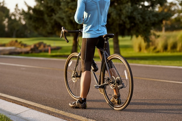 Vista traseira de um homem atlético em roupas esportivas em pé com uma bicicleta na estrada, andando de montanha