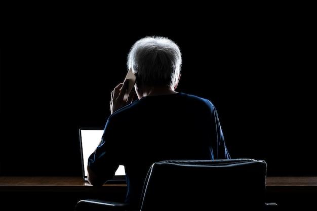 Vista traseira de um homem com cabelos grisalhos, trabalhando em casa tarde da noite, falando em seu telefone