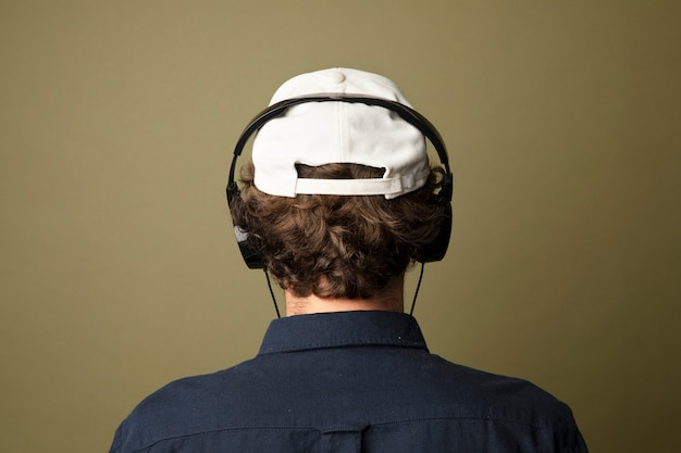 Vista traseira de um homem de boné branco ouvindo música usando fones de ouvido