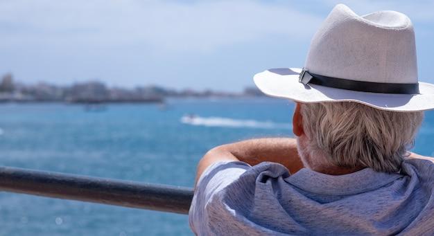 Vista traseira de um homem de cabelos grisalhos com chapéu, olhando a paisagem marinha e o horizonte sobre a água nas férias no mar