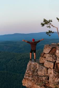 Vista traseira de um homem de pé no contexto das montanhas com os braços estendidos. o homem nas montanhas levanta as mãos. homem no fundo das montanhas. viajar para as montanhas
