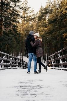 Vista traseira de um homem e uma mulher ao ar livre juntos durante o inverno