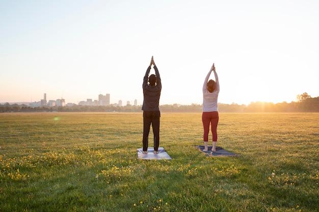 Vista traseira de um homem e uma mulher fazendo ioga juntos ao ar livre