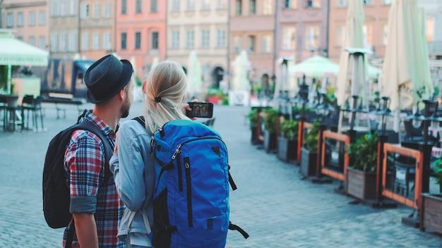 Vista traseira de um homem e uma mulher fazendo selfie em smartphone no centro da cidade
