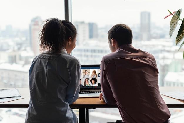 Vista traseira de um homem e uma mulher no escritório, tendo uma videochamada