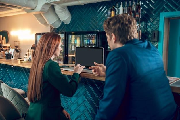 Vista traseira de um homem e uma mulher sentados perto do laptop