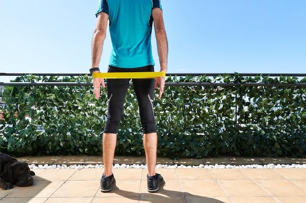 Vista traseira de um homem em roupas esportivas, estendendo-se com um elástico sendo observado por seu cachorro