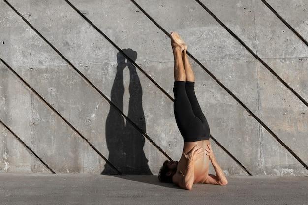 Vista traseira de um homem fazendo ioga ao ar livre