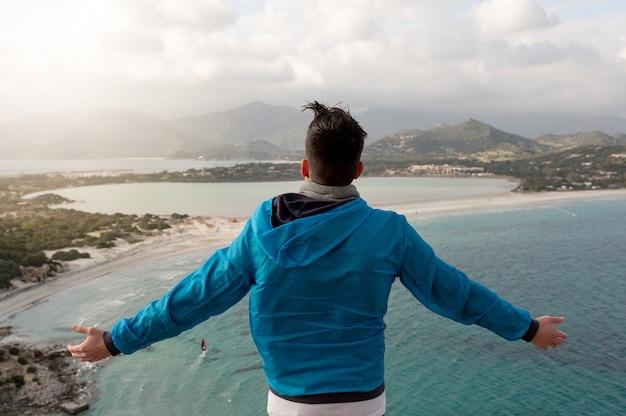 Vista traseira de um homem irreconhecível de pé em um penhasco com os braços abertos, aproveitando a brisa do mar e o vento