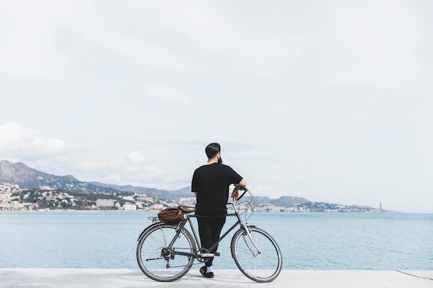 Vista traseira, de, um, homem jovem, ficar, com, bicicleta, olhando mar