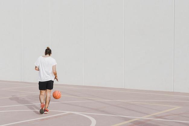 Vista traseira, de, um, homem jovem, praticando, basquetebol