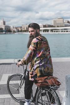 Vista traseira, de, um, homem jovem, sentar-se bicicleta, olhar ombro, perto, a, costa