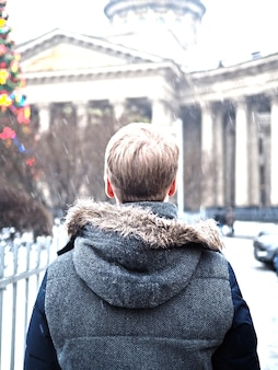 Vista traseira de um homem loiro olhando para a árvore de natal perto da catedral de kazan em são petersburgo