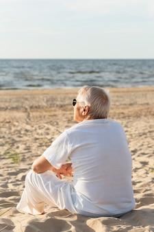 Vista traseira de um homem mais velho admirando a vista na praia enquanto descansava ao sol