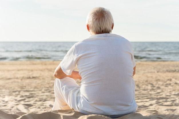 Vista traseira de um homem mais velho admirando a vista na praia