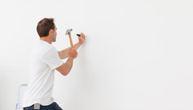 Vista traseira de um homem martelando contra uma parede branca