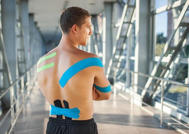 Vista traseira de um homem musculoso usando roupa esportiva preta, olhando para o lado
