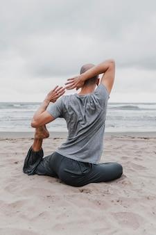 Vista traseira de um homem na praia fazendo ioga