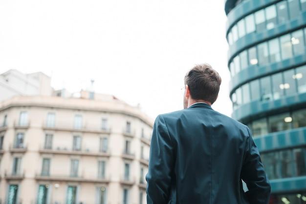 Vista traseira, de, um, homem negócios, olhar, incorporado, predios, cidade