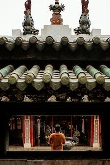 Vista traseira de um homem orando no templo com incenso