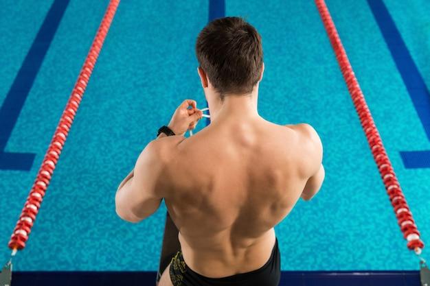 Vista traseira de um homem preparando óculos de natação